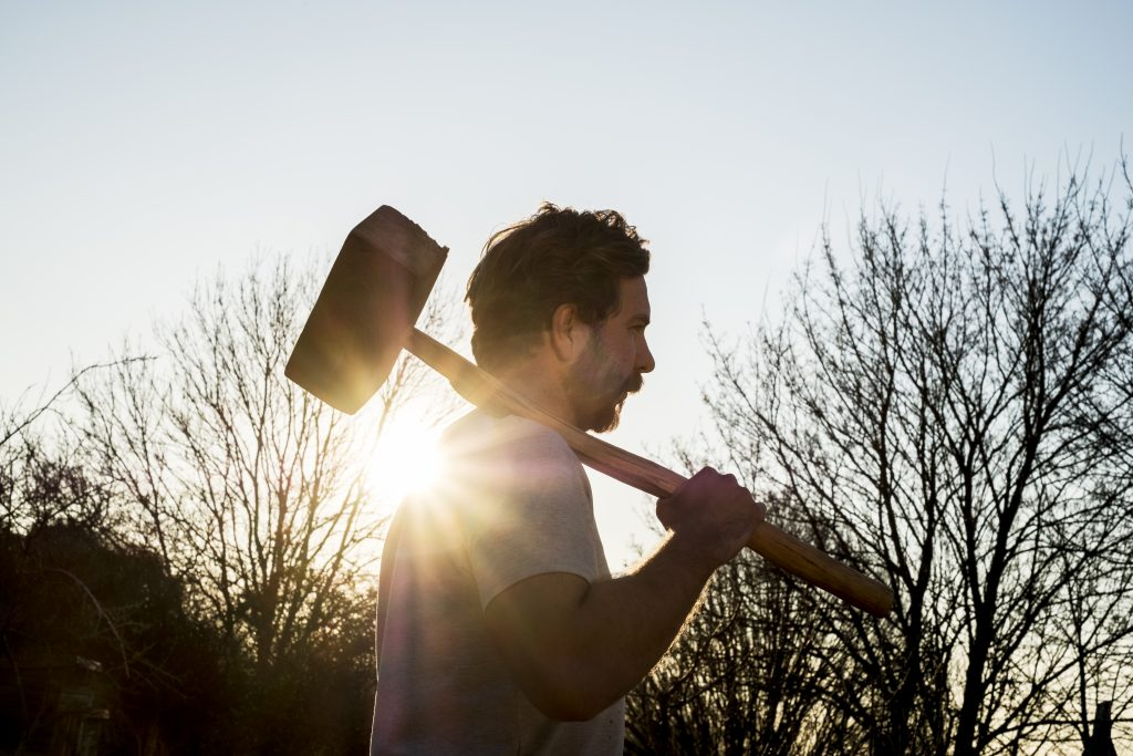 man with hammer preparing to smash marketing barriers