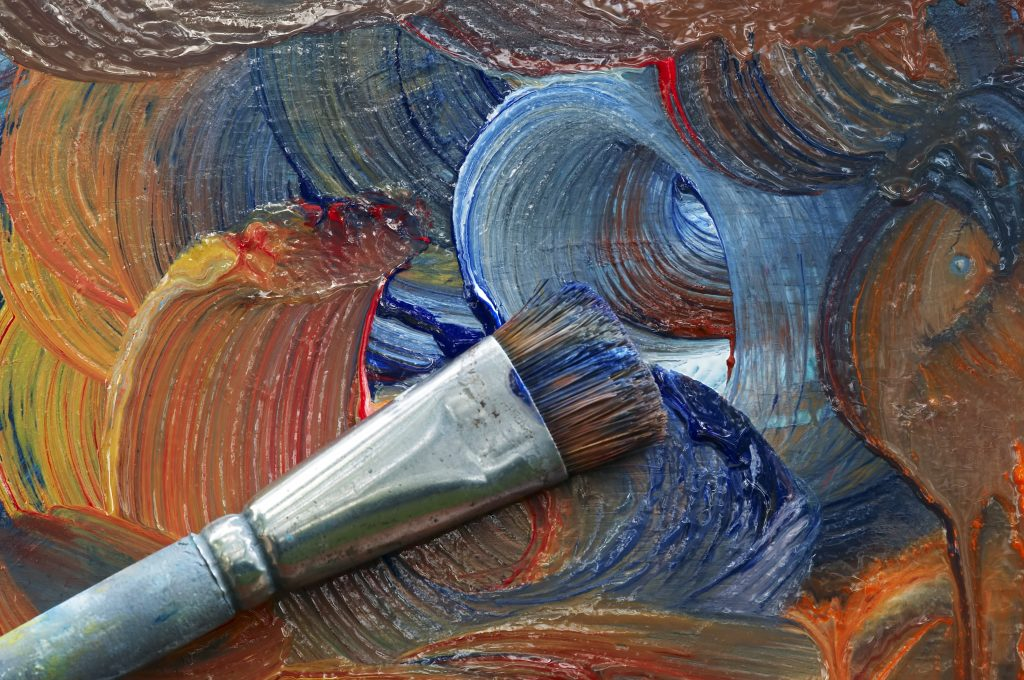 paintbrush with paint smeared on easel